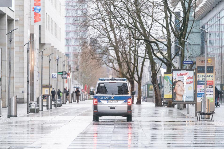 Ein Polizeiauto steht während des Lockdowns auf der fast menschenleeren Prager Straße in Dresden.