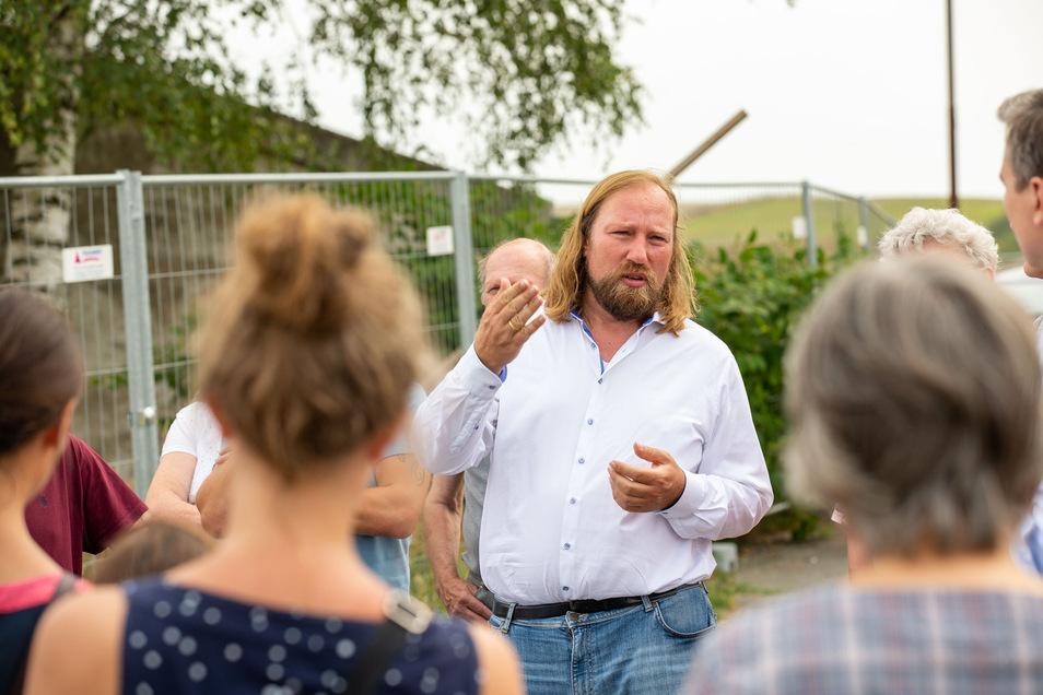 Anton Hofreiter, Fraktionschef der Grünen im Bundestag, spricht mit Anwohnern am Bauzaun der Schweinemastanlage von Langenwolmsdorf.