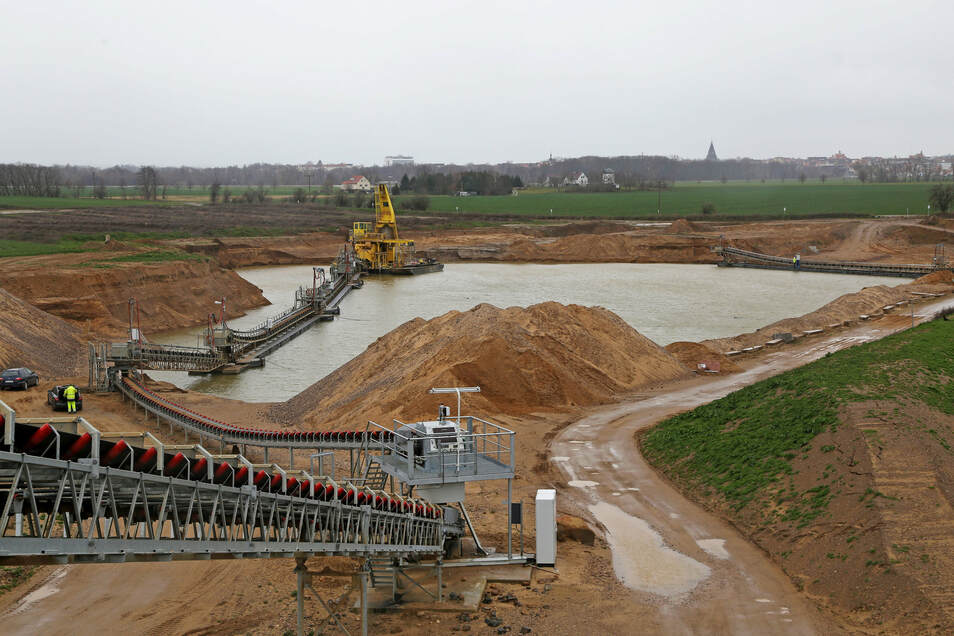 Ein Blick von der Brücke hinab auf den Kiessee, aus dem das Material gefördert wird. Im Hintergrund Riesa.