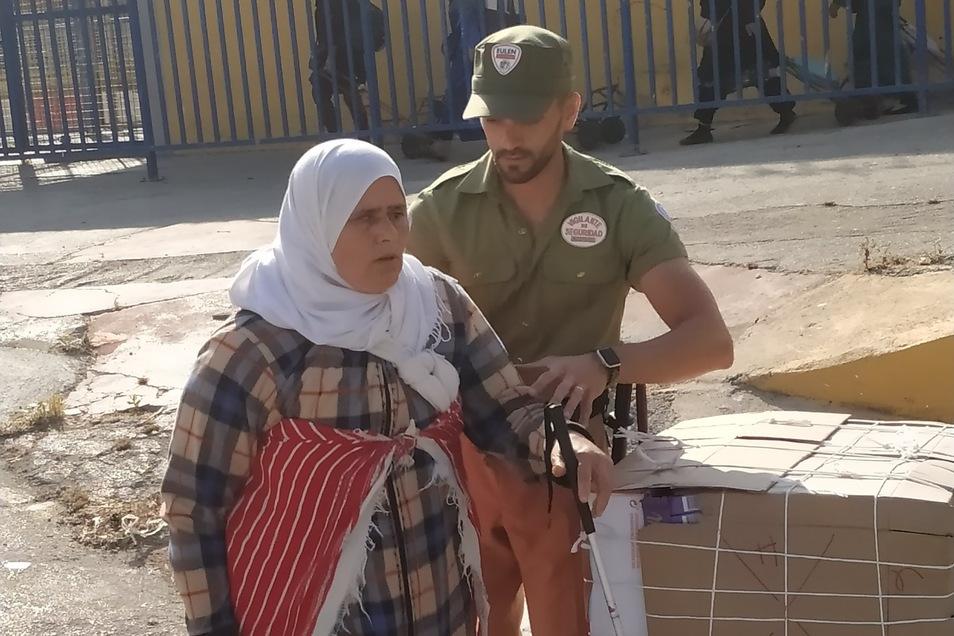 Auch die blinde Frau, die sich mit ihrem Stock vorwärts tastet und einen Karren hinter sich herzieht, bekommt Hilfe von den Wachleuten.