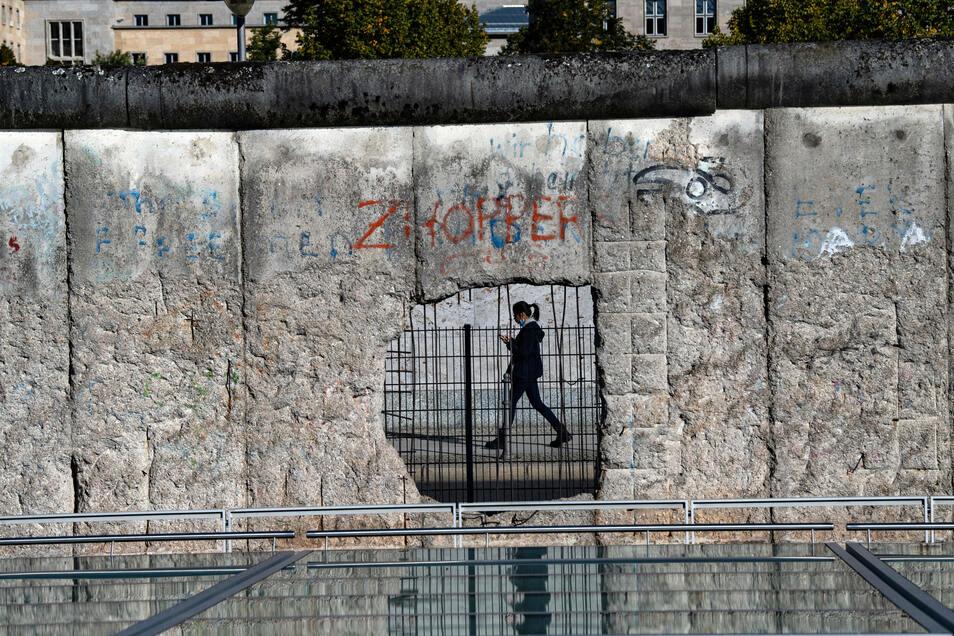Steinerner Zeuge der Teilung: Eine Frau ist durch ein Loch der ehemaligen Grenzmauer in Berlin zu sehen.