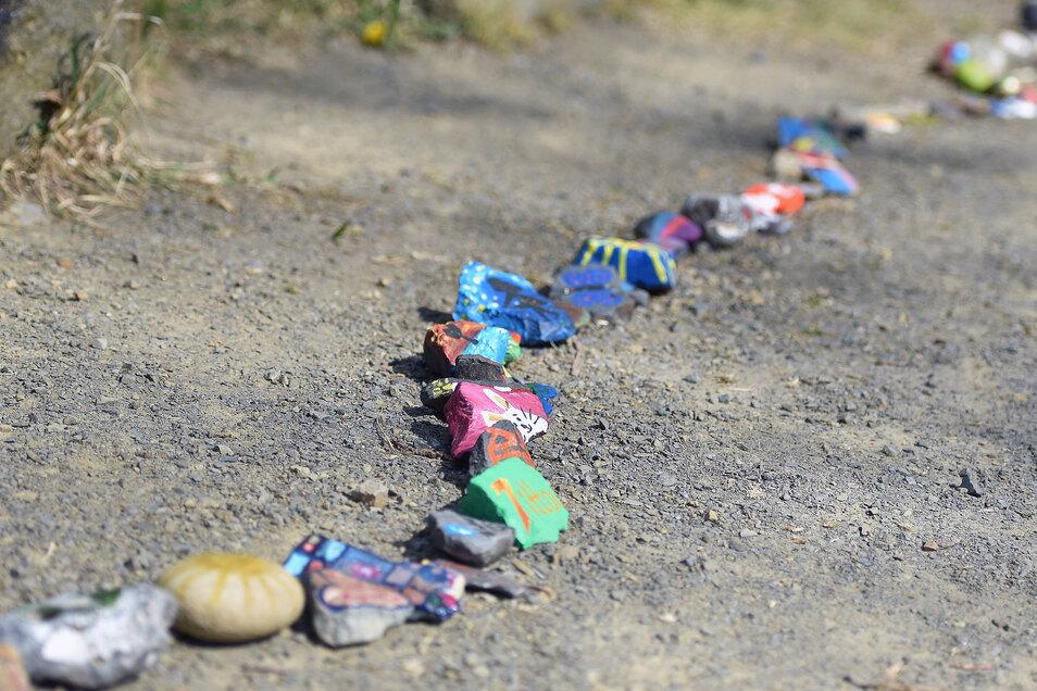 Der Wartewurm am Pethauer Teich besteht aus etlichen bunt angemalten Steinen.