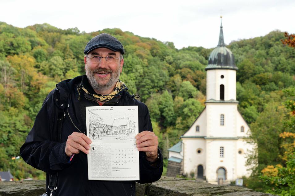 """Kai Tempel steht mit seinem neuen Kalender """"Dörfer am und im Tharandter Wald"""" auf der Burgruine Tharandt mit der Kirche im Hintergrund. Beides Motive, die er auch gezeichnet hat."""