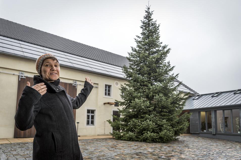 Die Gröditzer Stadtbibliotheksleiterin Inka Wirtjes präsentiert den diesjährigen Gröditzer Weihnachtsbaum im Dreiseithof. Am Donnerstag wurde er aufgestellt.