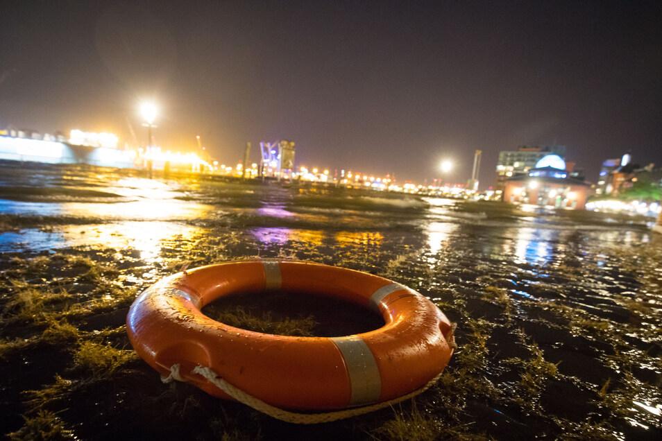 Ein Rettungsring liegt am 13. September 2017 im Hafen von Hamburg am Rande des überschwemmten Fischmarkts vor den Fischauktionshallen (Symbolfoto).