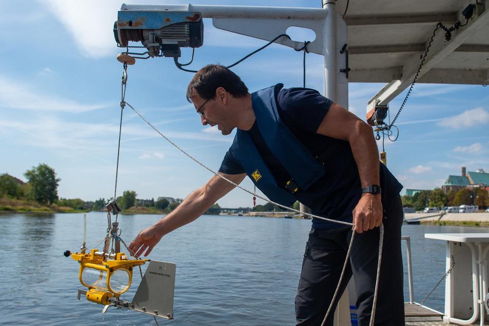 """Der Wissenschaftler Norbert Kamjunke vom Helmholtz Zentrum für Umweltforschung lässt vom Forschungsschiffes """"Albis"""" einen Horizontalwasserschöpfer in die Elbe hinab."""