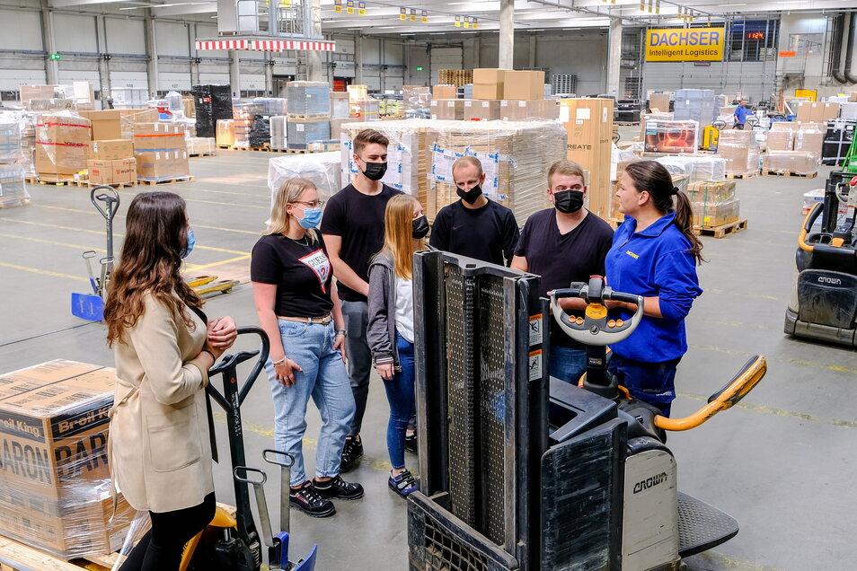 Ausbilderin Constanze Dittmann (rechts) erklärt den neuen Azubis, was wie in der großen Lagerhalle funktioniert.