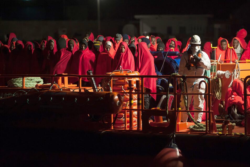 Eine Gruppe von Migranten, die von den spanischen Seebehörden gerettet wurden, steht auf einem Rettungsschiff, als sie im Hafen von Malaga ankommen.