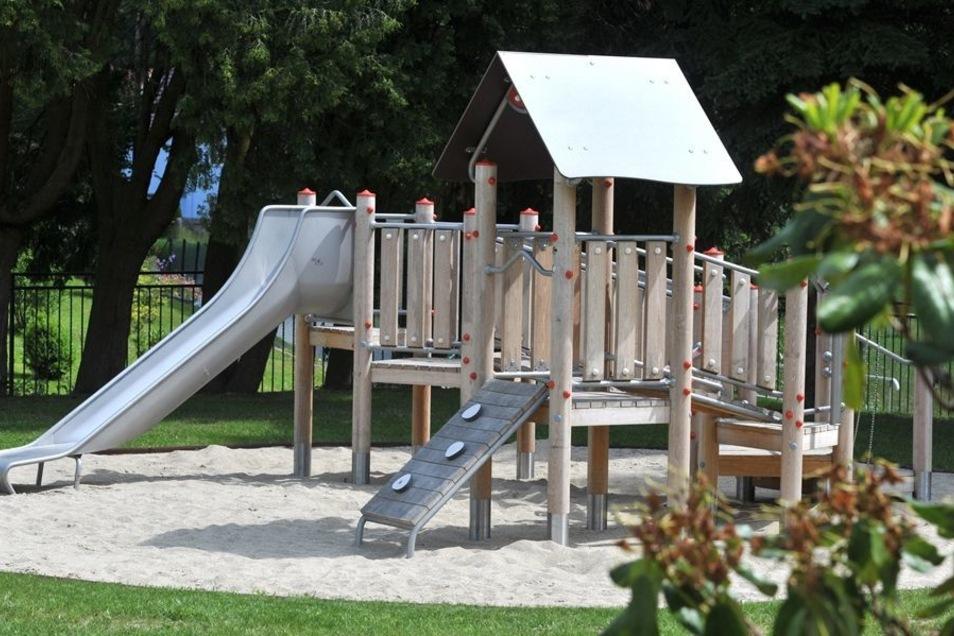 Ein schöner Garten mit viel Grün und zwei Spielanlagen aus Holz warten auf die Mädchen und Jungen.