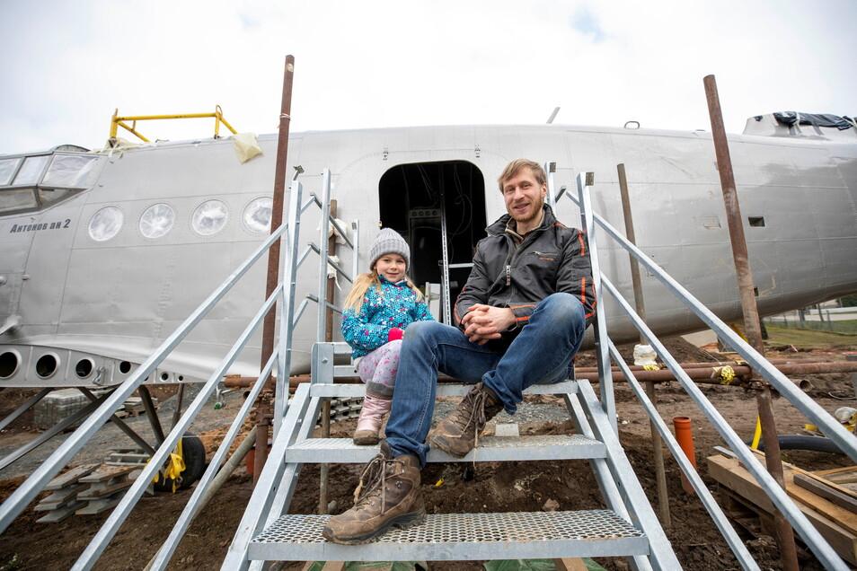 Erik Herbert mit seiner Tochter Klara sitzen auf der Treppe zum Eingang der Antonov.