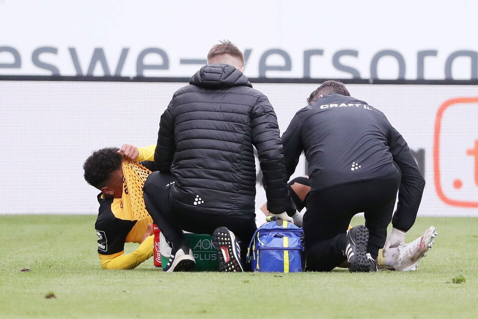 Ransford-Yeboah Königsdörffer mag gar nicht hinschauen, während sich die Betreuer um sein linkes Knie kümmern. Der 19-Jährige muss ausgewechselt werden.