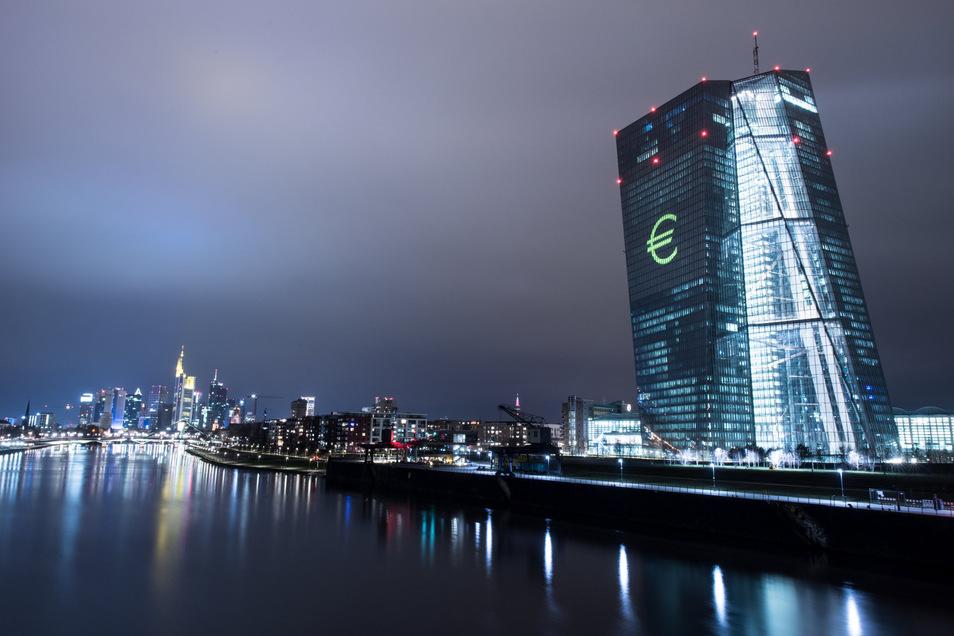 Die Europäische Zentralbank (EZB) ist in Frankfurt/Main mit einem Eurozeichen illuminiert.