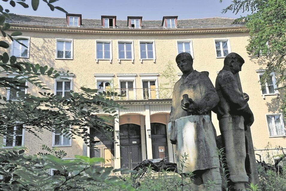 Die 1953/54 vom VEB Kreisbau Niesky gebaute Glasfachschule liegt schon seit viel Jahren brach. Auf den Balkon über dem Eingang wachsen Bäume. Auch die plastische Figurengruppe davor – bestehend aus einem Glasmacher, einem Techniker und einer Schleiferin –
