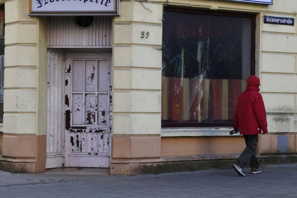 Ein Mann geht in Bremerhaven an dem kaputten Fenster einer geschlossenen Gaststätte vorbei (Symbolfoto).