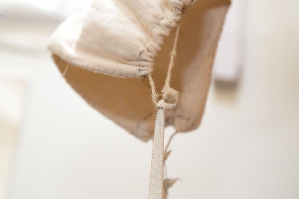Die Schnur oder das Band kurz halten und fest verknoten. Das wird auf der anderen Seite wiederholt. Beide Seiten werden mit einem Gummiband verbunden. Die Länge des Gummibands muss individuell nach der Kopfgröße angepasst werden.