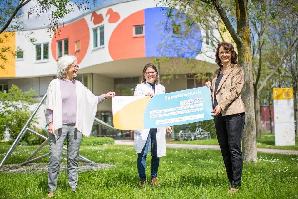 Ursula Herrmann (l.) und Cornelia Bohn (r.) übergeben eine Spende im Namen des Sonnenstrahl e.V. an Professorin Julia Hauer. Sie leitet die Kinderonkologie am Dresdner Universitätsklinikum.