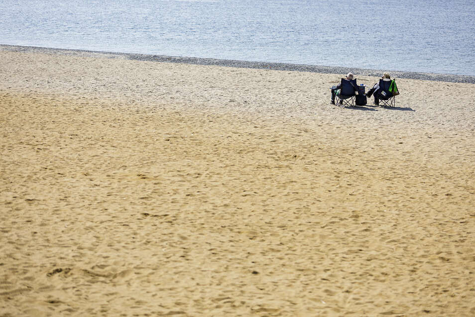 Zwei Menschen sitzen auf Campingstühlen am Berzdorfer See. Wohl wegen der Ausgangsbeschränkungen und sicher auch wegen der für Autos gesperrten Zufahrten ist hier aktuell auch bei schönem Wetter nicht viel los.