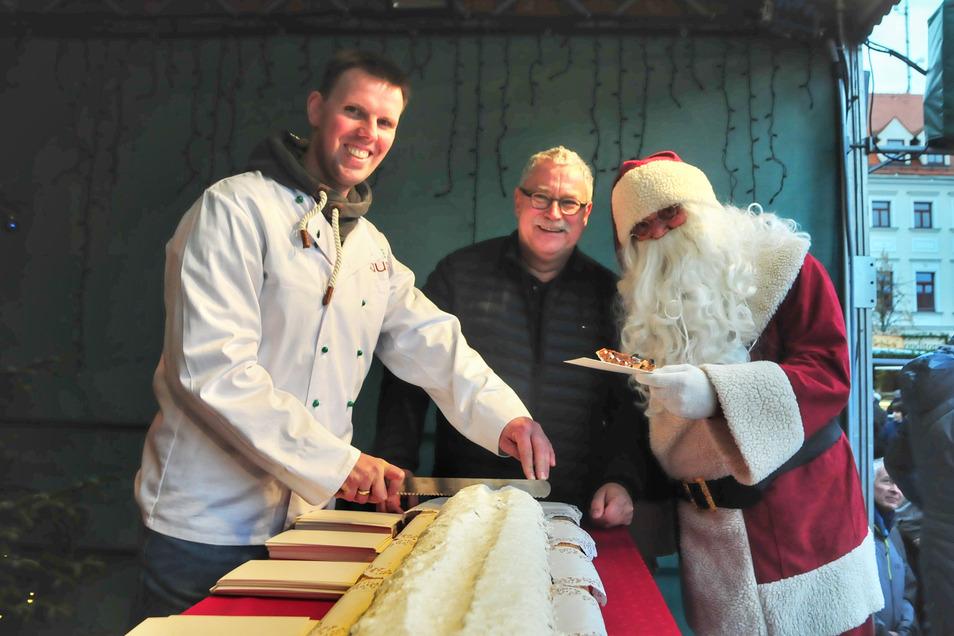 Bäcker Sebastian Faust, Bürgermeister Tilo Hönicke und der Weihnachtsmann am Riesenstollen aus dem Hause Faust.