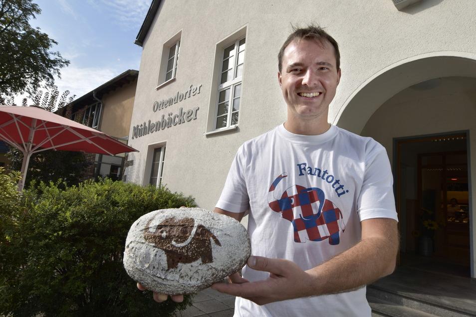 """Robert Meyer mit dem Maskottchen """"Fantotti"""" auf dem T-Shirt und dem dazugehörenden Brot."""