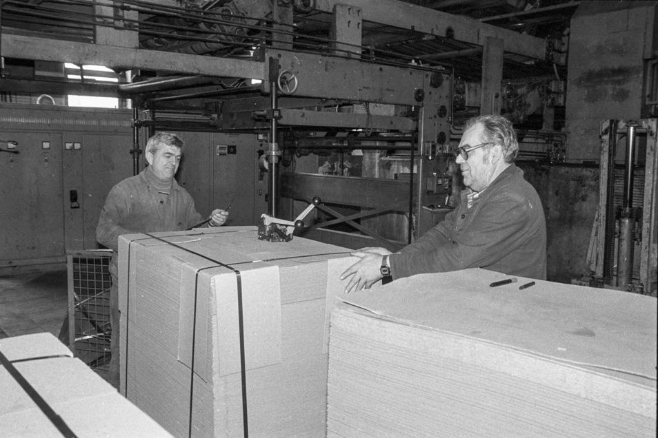 Die letzten Mitarbeiter Heinz Habla (re.) und Manfred Fetting bei der manuellen Umreifung einer Kartonplatte. Dahinter befindlich die Klebemaschine, denn die Kartonbahnen wurden zu dicken Buchbahnen zusammengeklebt. Buchdeckel-Karton, der für Kinderbücher