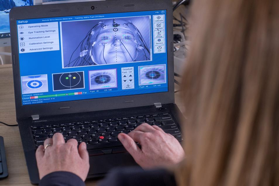 Am Monitor werden Veränderungen in der Pupillengröße bei der Verarbeitung von Störgeräuschen gemessen.