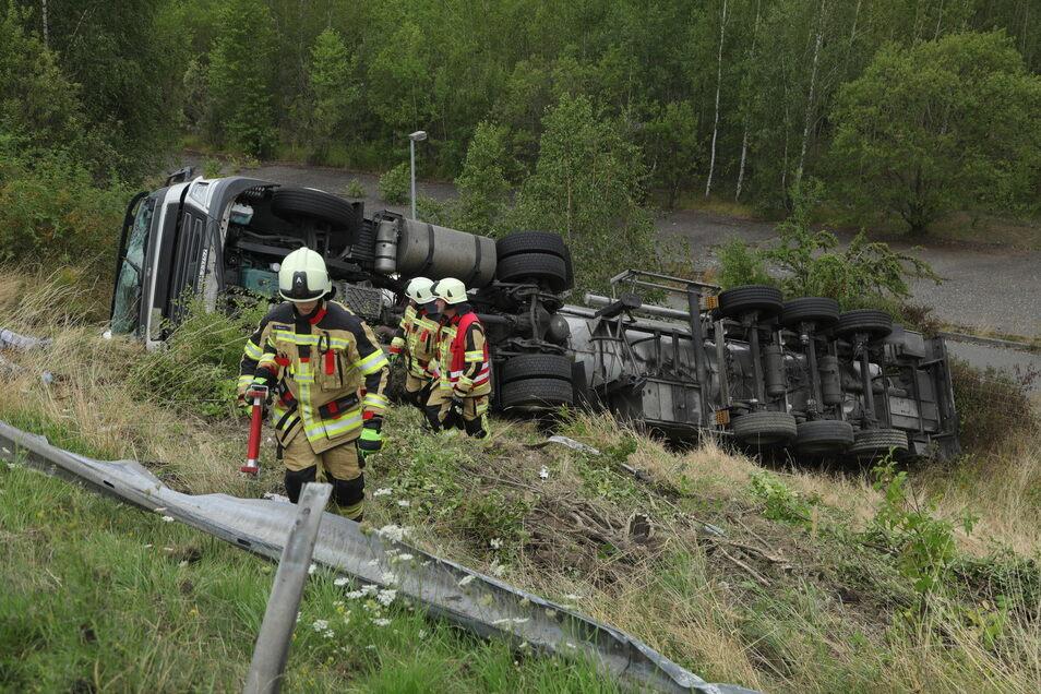 Feuerwehrleute müssen den umgekippten Laster bergen.
