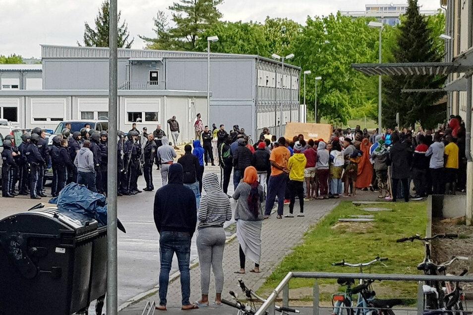 Polizisten (l.) und Bewohner stehen am Sonnabend vor dem Ankerzentrum in Regensburg.