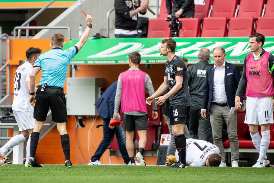 Schiedsrichter Robert Schröder (l) zeigt Christian Groß (M) von Werder Bremen die rote Karte. Am Boden liegt der gefoulte Florian Niederlechner vom FC Augsburg.