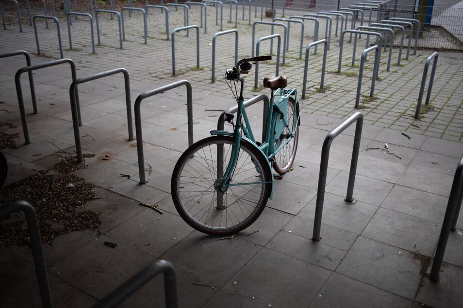 Ein einzelnes Fahrrad steht auf dem Stellplatz einer Schule. Dieses Bild soll sich ab der nächsten Woche in Sachsen wieder ändern. Zunächst dürfen die Abitur- und Abschlussklassen wieder richtig lernen.