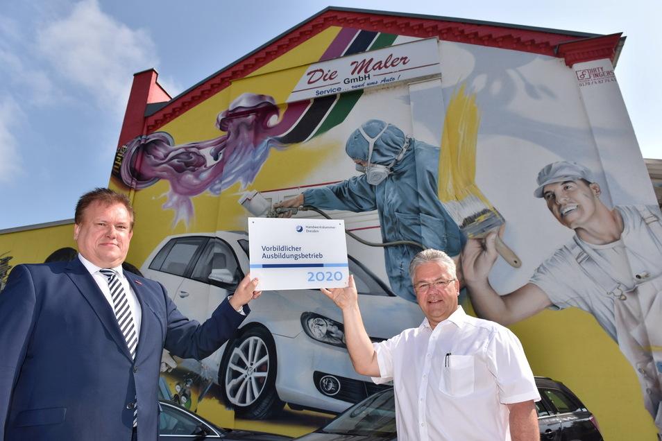 Andreas Brzezinski (l.), Hauptgeschäftsführer der Handwerkskammer Dresden übergibt Mario Schneider, Geschäftsführer der Maler GmbH, das Schild für die Auszeichnung.