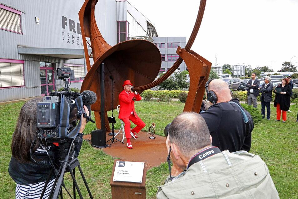 Zig Kameras waren am Montag auf Jörg Wachsmuth gerichtet. Der Profimusiker (roter Anzug) spielte das Riesen-Horn vor der Rime-Freyler-Halle in Gröba.