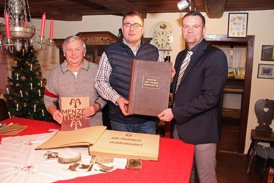 Arne Schiedt (Mitte) übergibt die Chronik an Bürgermeister Stefan Schneider (r.) und Museumsleiter Mathias Hennig.