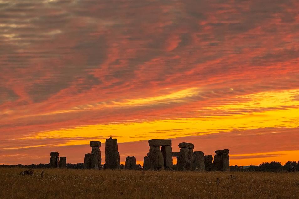 Der Sonnenaufgang färbt den Himmel über Stonehenge in orange-gelbes Licht.