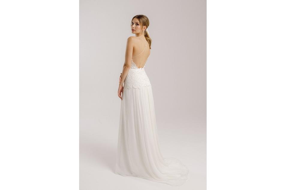 Dieses Kleid entzückt mit einem tiefen Rückenausschnitt und einem mehrlagigen Rock .