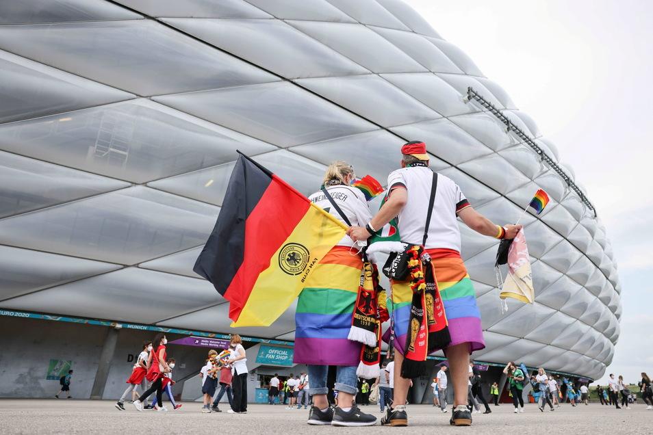 Deutsche Fußballfans kommen zum Stadion. Es sind viele Deutschland- und einige Regenbogen-Fahnen zu sehen.