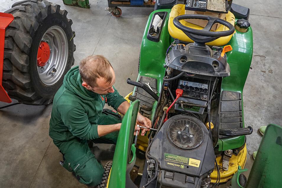 Der Rasentraktor sagt keinen Ton mehr. Deshalb wechselt Patrick Schubert den Anlasser – und schon rollt die Maschine wieder.