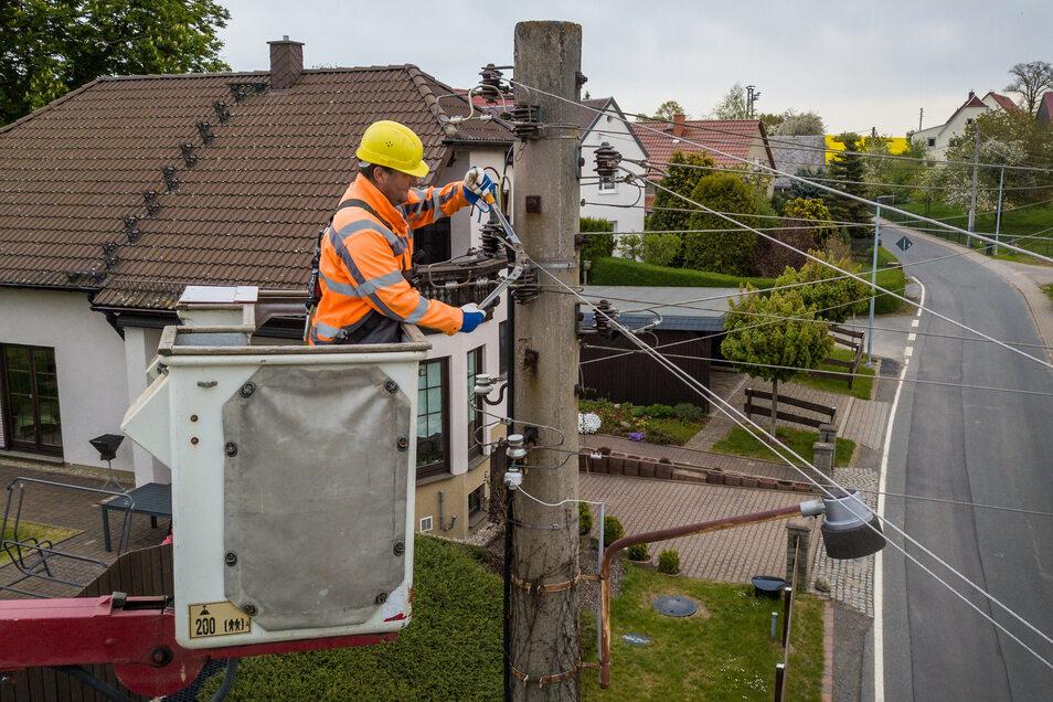 Frank Goldbach von der Firma Klaus Bauer GmbH Elektroanlagen aus Döbeln demontiert eine alte Aluminiumleitung in Gadewitz bei Großweitzschen. Die Leitung wird durch Erdkabel ersetzt.
