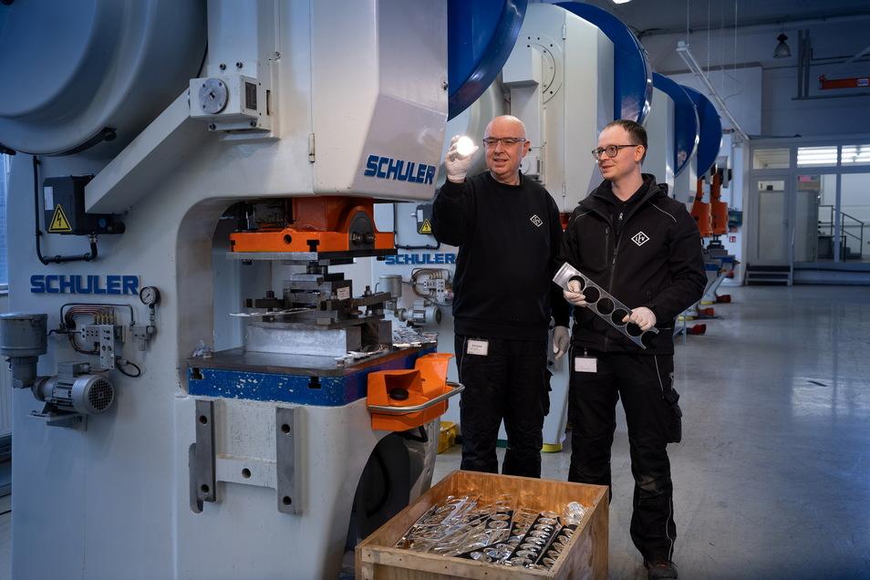 Teures Licht: Firmengründer Adelbert Geiger und sein Sohn Andreas halten an einer Stanzmaschine eine Silbermünze ins Blitzlicht.