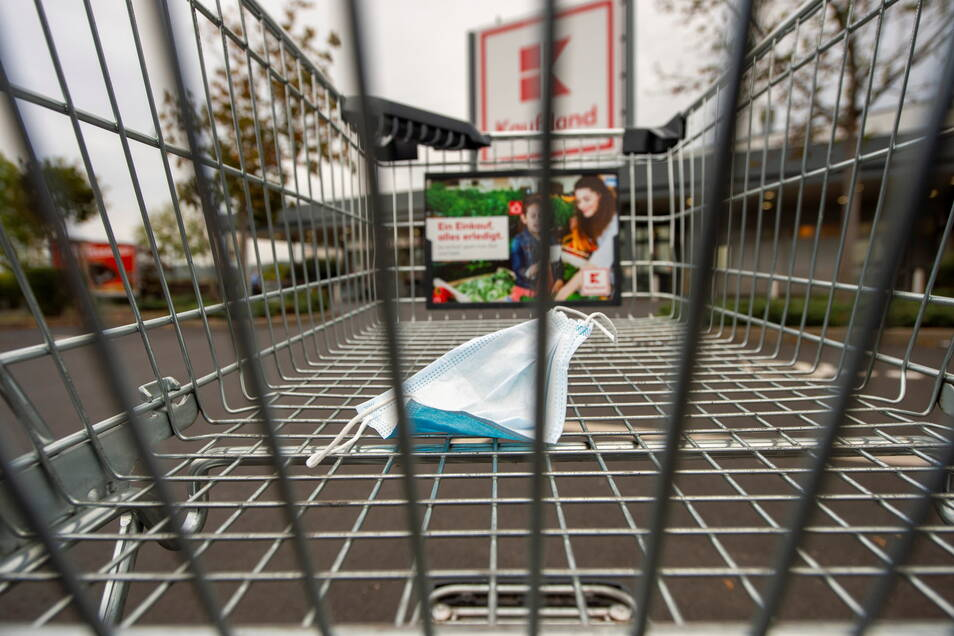 Eine Mund-Nasen-Maske liegt in einer gestellten Szene in einem Einkaufswagen vor dem Supermarkt von Kaufland.
