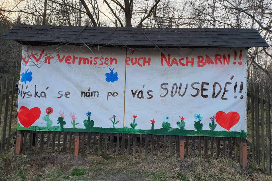"""""""Wir vermissen euch Nachbarn"""" steht auf einem Leinentuch, das beim Oybiner Ortsteil Hain auf tschechischer Seite an einem Zaun hängt."""