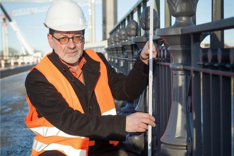 Straßenbauamtschef Reinhard Koettnitz demonstriert mit dem Zollstock, dass das nachgebaute historische Geländer nicht die nötige Höhe erreicht.