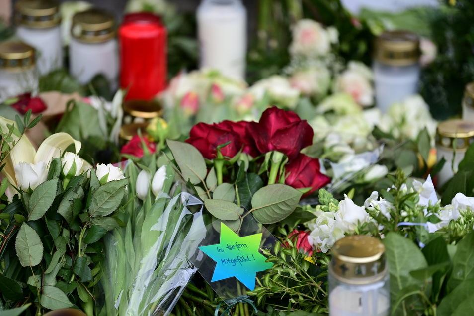 """Blumen, Kerzen und ein Zettel mit der Aufschrift """"In tiefem Mitgefühl!"""" liegen vor dem Eingang zur Einrichtung des diakonischen Anbieters Oberlinhaus in Potsdam."""