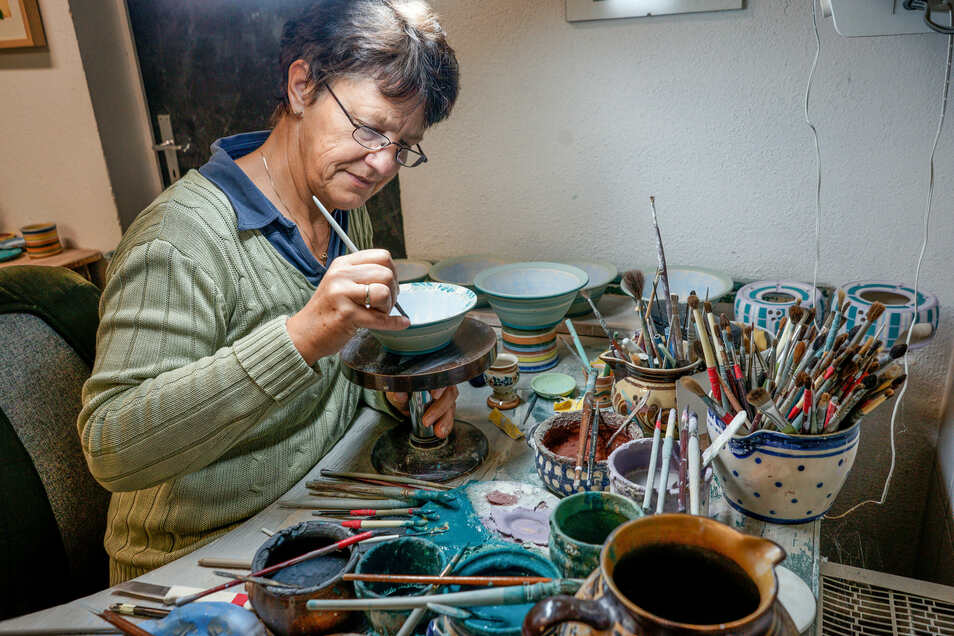 Keramikmalerin Ilona Schwiebs gehört zum Team der Töpferei. Sie bemalt die farbigen Keramik-Schalen mit Blumenornamenten. Die Farben werden durch das anschließende Brennen noch intensiver.