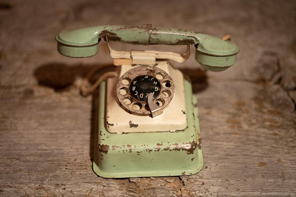 """Rolf U., Jahrgang 1936, spielte gern mit Spielzeugsoldaten und mit diesem Telefon. Am 8. Mai 1945 sah er Flugzeuge, aus denen etwas herausfiel, das aussah """"wie Maden"""". Schreiend lief er zur Mutter, die ihn zu Boden warf, sich selbst darüber. Eine Bombe fi"""