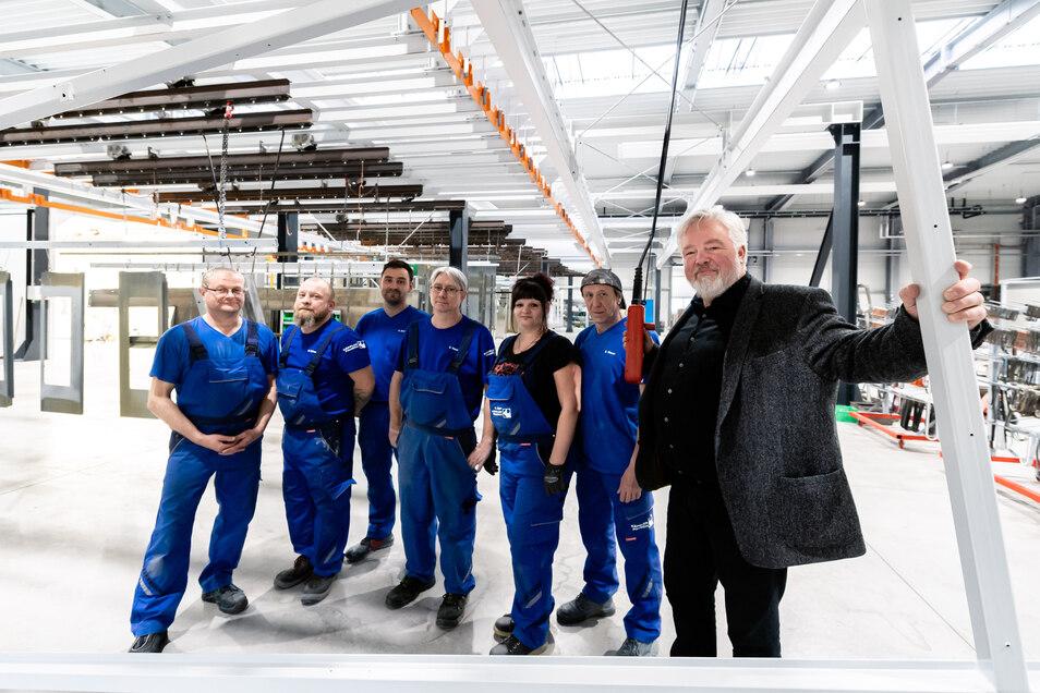 Bei Käppler & Pausch ist man stolz auf die neue Farbgebung – das Foto zeigt den Geschäftsführer Klaus Gerlach und einige Mitarbeiter. Die Logistik in der Halle läuft über ein oberirdisches Schienensystem. Mittels Knopfdruck lassen sich darauf auch schwere