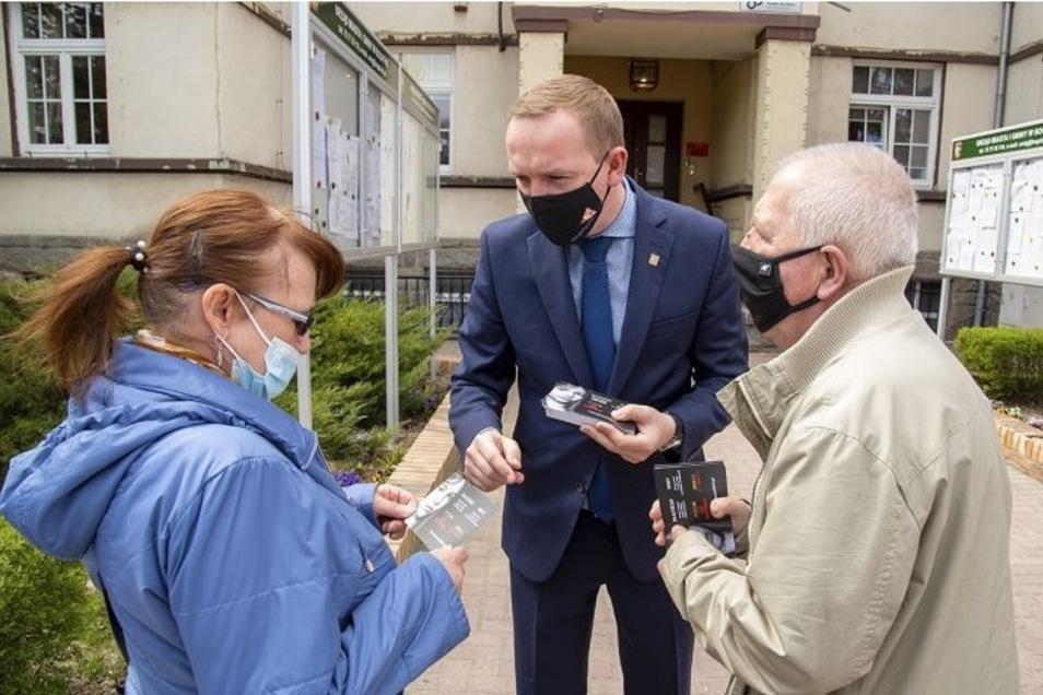 Bürgermeister Wojciech Dobrołowicz verteilt Postkarten an die Bewohner seiner Stadt.