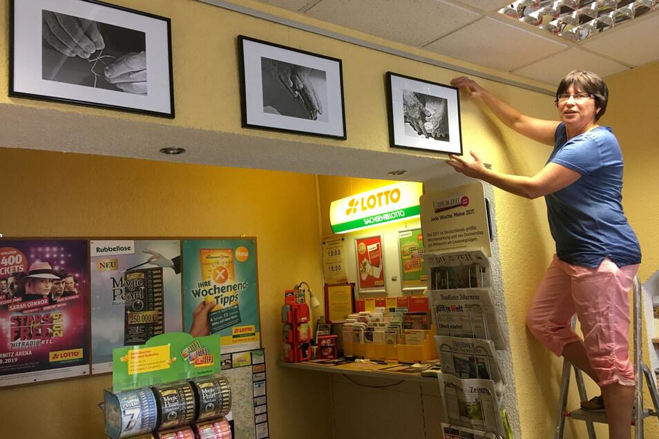 Suela Riedel hängt die Fotos der ersten Ausstellung im Laden auf.