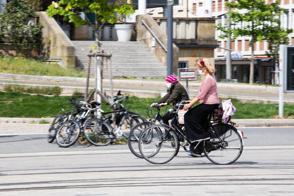 Zwei Frauen mit Mund- und Nasenschutz fahren auf Fahrrädern