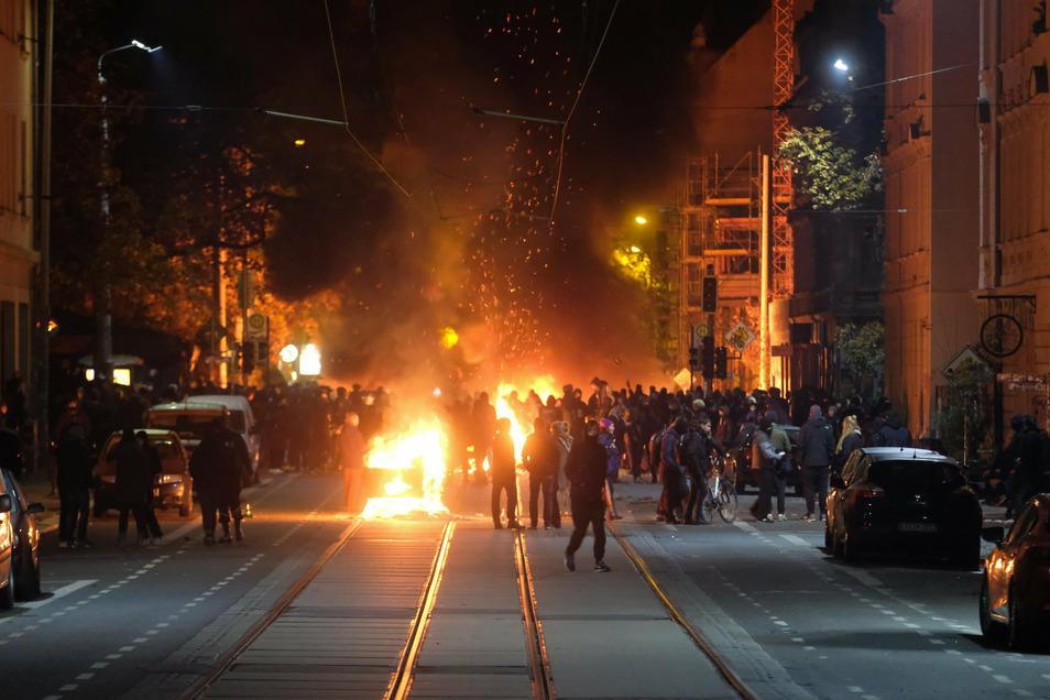 Menschen stehen an brennenden Barrikaden bei Ausschreitungen in Connewitz.