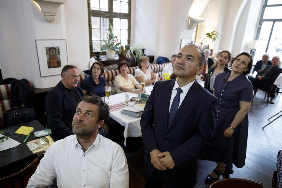 Octavian Ursu (Mitte) schaut sich die Wahlberichterstattung im Kreise seiner Familie und seiner CDU-Mannschaft im Ratscafé am Untermarkt an.